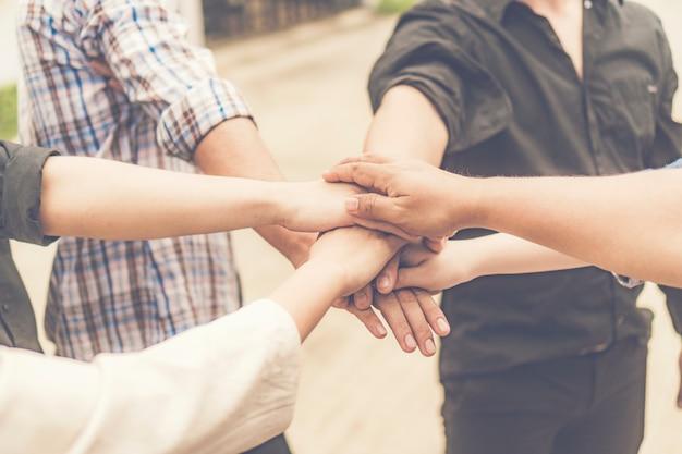 Groep van mensen uit het bedrijfsleven gekruist armen in stapel voor de overwinning. stack van handen