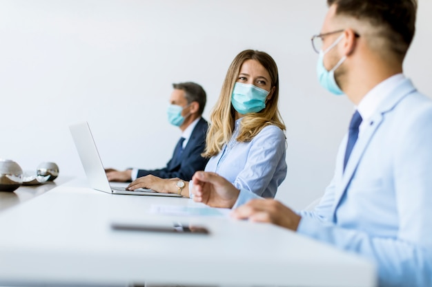 Groep van mensen uit het bedrijfsleven hebben een vergadering en werken op kantoor en dragen maskers als bescherming tegen corona-virus