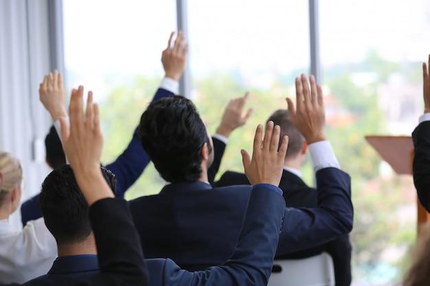 Groep van mensen uit het bedrijfsleven in seminar of vergadering door focus op hand opstaan