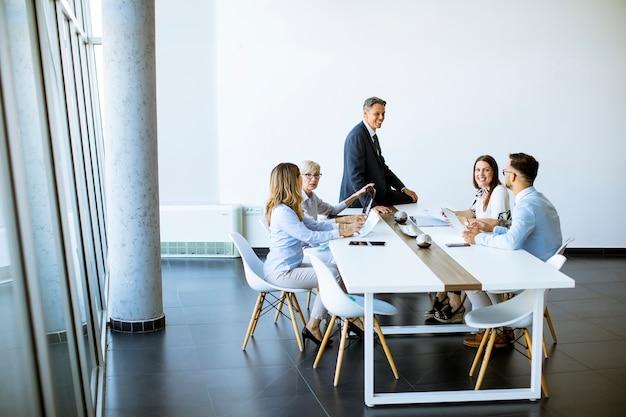 Groep van mensen uit het bedrijfsleven met jonge volwassenen en senior vrouw collega over bijeenkomst in het moderne, lichte kantoor interieur
