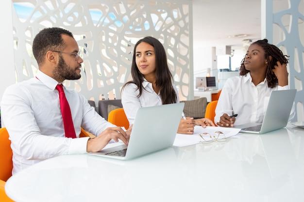 Groep van mensen uit het bedrijfsleven praten tijdens vergadering