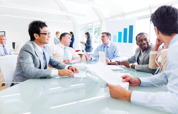 Groep van mensen uit het bedrijfsleven rond de vergadertafel met elkaar praten.