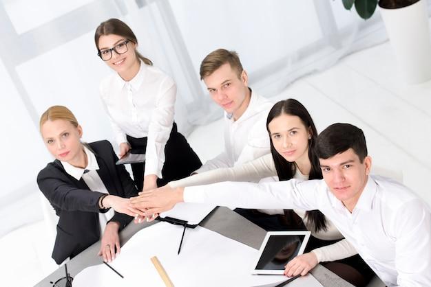 Groep van mensen uit het bedrijfsleven stapelen elkaar overhandigen aan het bureau