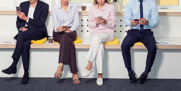 Groep van mensen uit het bedrijfsleven, zonder gezichten, met behulp van smartphones zittend op kantoor.