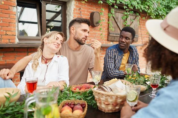 Groep van mooie jonge mensen genieten van diner buiten zittend aan een houten tafel bij huisje