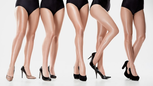 Groep van mooie jonge vrouwen die zich voordeed in de studio op een witte achtergrond. vrouwelijk schoonheidsconcept. de schoenen met hoge hakken op blanke modellen