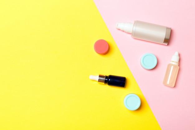 Groep van plastic bodycare fles plat lag samenstelling met cosmetische producten op gele en roze achtergrond. set van witte cosmetische containers, bovenaanzicht met kopie ruimte
