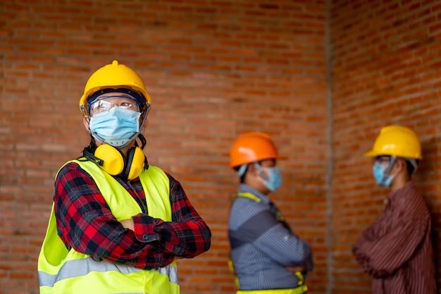 Groep van professioneel engineeringteam draagt beschermende veiligheidsmaskers voor coronavirus disease 2019 (covid-19) in de industriële machinefabriek.