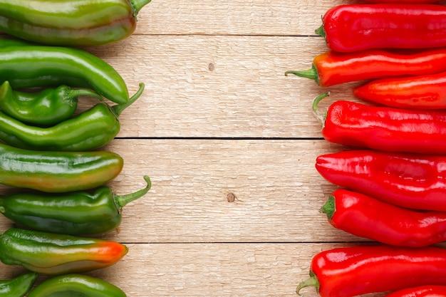 Groep van rode en groene paprika's op oude houten tafel
