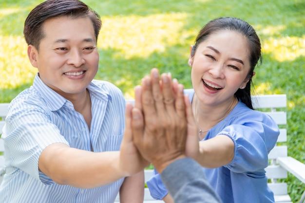 Groep van senior aziatische gepensioneerde geven high five bouwen van succesvol team.
