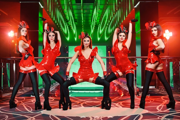 Groep van sexy vrouwelijke dansers in rode bijpassende outfits presteren