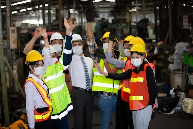 Groep van teamwerklid dat hand doet opstaan en vrolijk als eenheidsteam.