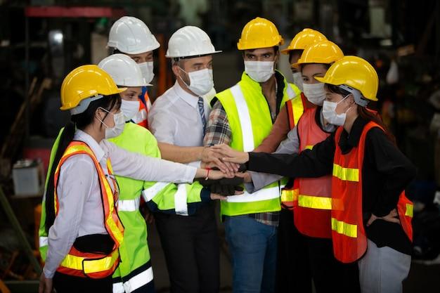 Groep van teamwerklid uit de industrie die handbewegingen doet als eenheid.