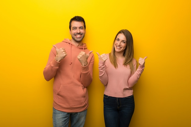 Groep van twee mensen op gele achtergrond die duimen op gebaar geeft