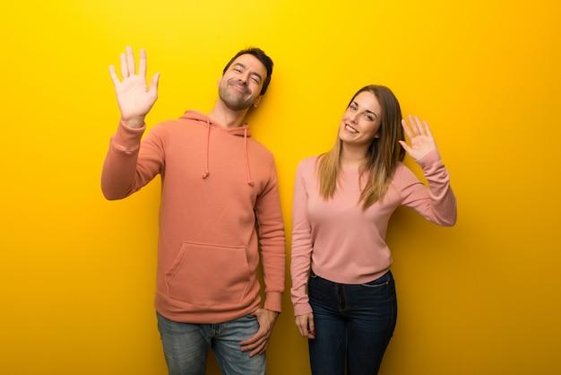 Groep van twee mensen op gele achtergrond die met hand met gelukkige uitdrukking groeten