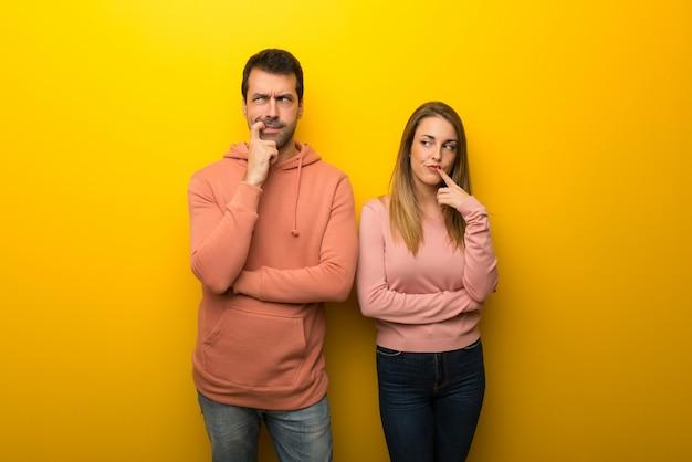 Groep van twee mensen op gele achtergrond die twijfels hebben terwijl het omhoog kijken