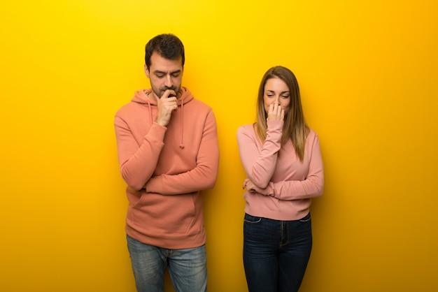 Groep van twee mensen op gele achtergrond die twijfels hebben