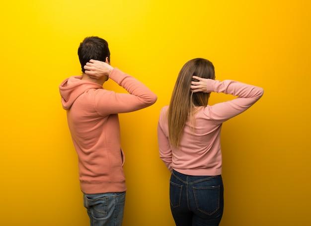 Groep van twee mensen op gele achtergrond op achterpositie die terug eruit zien