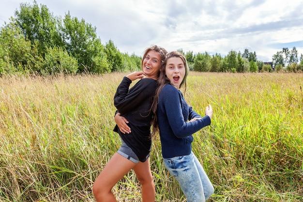 Groep van twee vriendinnen zusters dansen knuffelen en plezier samen in de natuur buiten