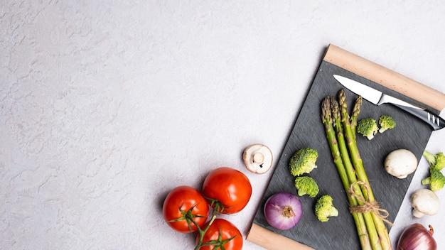 Groep van verse groenten op grijze achtergrond, plat leggen
