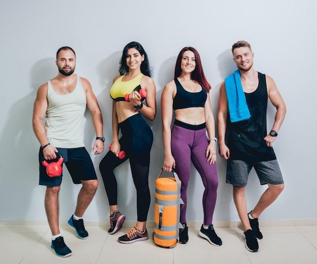 Groep van vier atletische jonge vrienden die zich in gymnastiek op de grijze muur verenigen