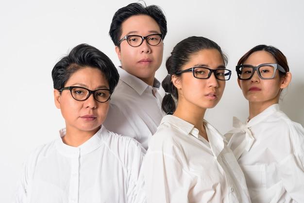 Groep van vier aziatische zakenmensen als team samen tegen een witte muur