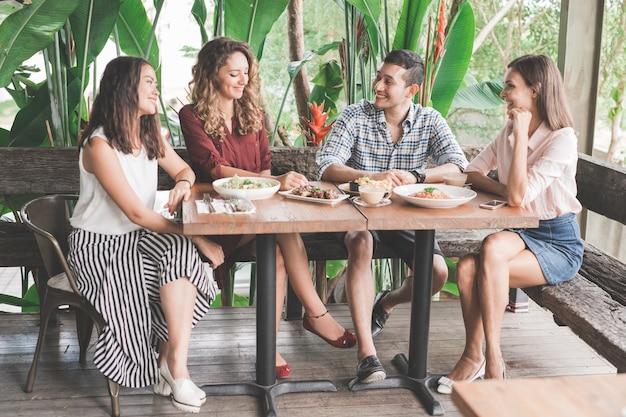 Groep van vier beste vrienden die samen lunchen in een café