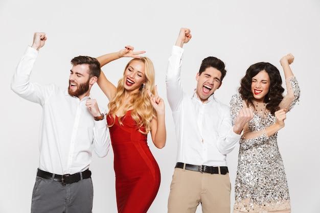 Groep van vier gelukkige mensen slim gekleed nieuwjaar vieren geïsoleerd over wit, dansen