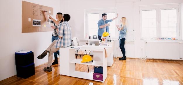 Groep van vier jonge gefocuste succesvolle zakenmensen die creatieve ideeën delen voor een pauze op kantoor terwijl ze samen tijd doorbrengen.