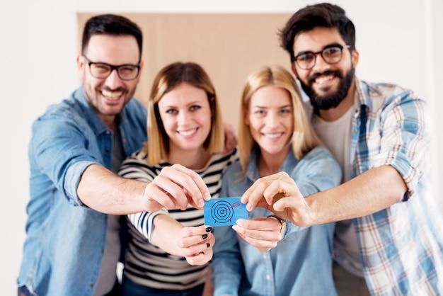 Groep van vier jonge gemotiveerde bedrijfsmensen die een blauw document met doel en pijl in het midden bij elkaar houden.