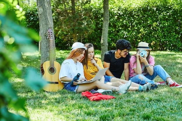 Groep van vier jonge mensen die pret in park hebben, zittend op het gras