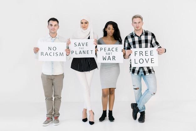 Groep van vier jonge multiraciale diverse mensen die naar de camera kijken, posters vasthouden met verschillende sociale slogans, geen oorlog, vrije liefde, red de aarde, geen racisme