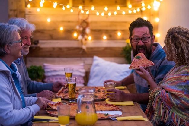 Groep van vier mensen die samen thuis of in een restaurant eten met pizza's en bieren - grappige scène van een vrouw die een pizza geeft aan zijn man of vriend