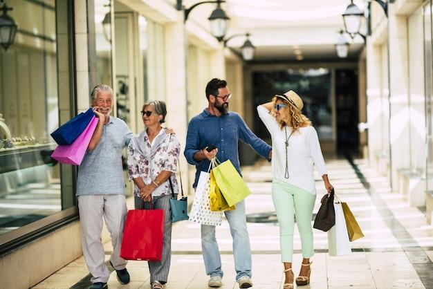 Groep van vier mensen ging naar het winkelcentrum om samen te winkelen met boodschappentassen aan hun handen - senioren en volwassenen in de winkels