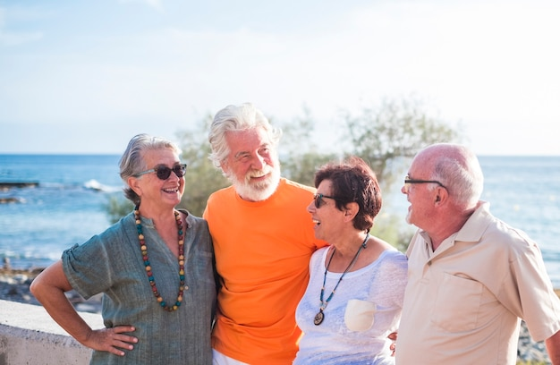 Groep van vier senior en volwassen mensen met een vriendschap op het strand praten en samen genieten - zee op de achtergrond