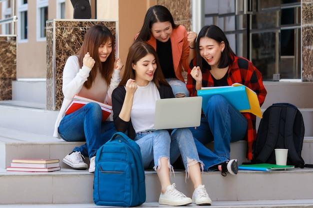 Groep van vier studentenmeisjes die boeken en een notebookcomputer vasthouden die samen zitten en praten