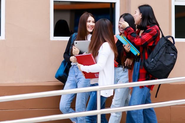 Groep van vier studentenmeisjes die samen lopen en praten met intiem.