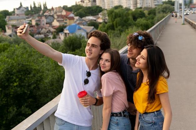 Groep van vier vrienden die samen buiten tijd doorbrengen en selfie maken