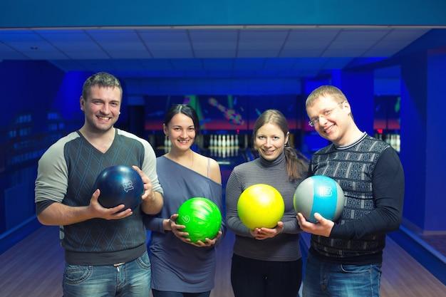 Groep van vier vrienden in een bowlingbaan met plezier