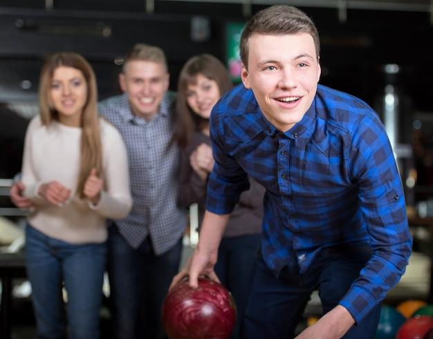 Groep van vier vrienden in een bowlingbaan plezier.
