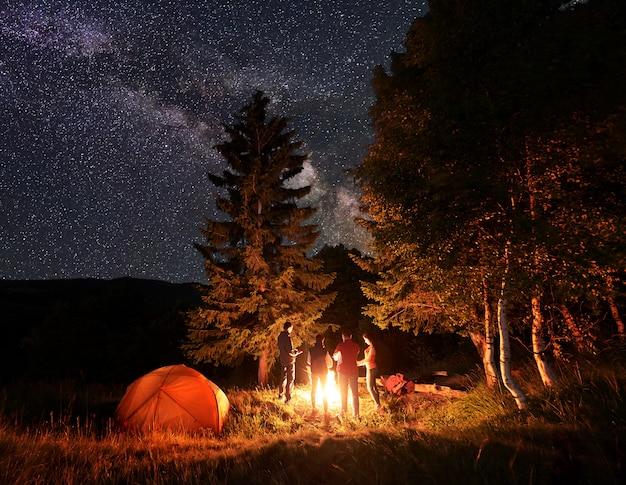Groep van vier vriendenwandelaars die hun handen rond een kampvuur verwarmen, rustend dichtbij gloeiende oranje tent onder ongebruikelijk sterrenhemel