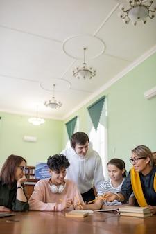 Groep van vijf tieners die een van romans bespreken tijdens het voorbereiden van les literatuur door bureau in universiteitsbibliotheek