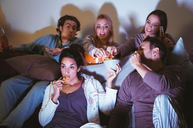 Groep van vijf vrienden die op een film letten