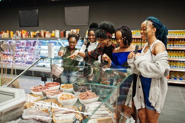 Groep van vijf vrouwen die vleesgerechten in de supermarkt kopen