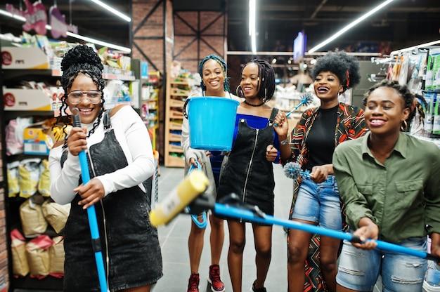 Groep van vijf vrouwen met stofwisser, toiletborstel en emmer die pret in de afdeling van huishouden schoonmakende punten in supermarkt hebben