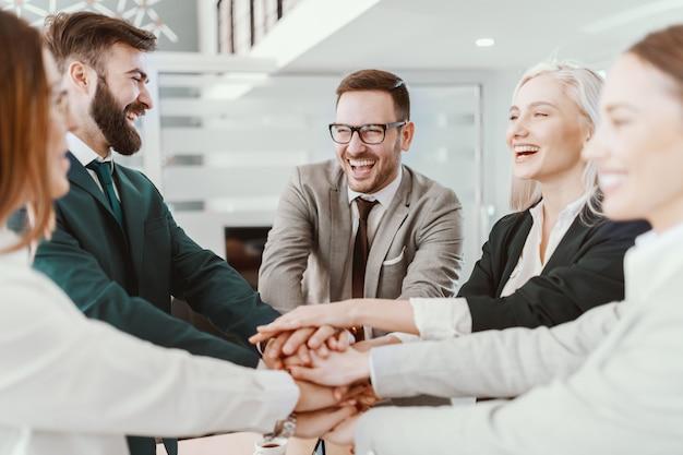 Groep van vrolijke blanke mensen uit het bedrijfsleven in formele slijtage handen stapelen na presentatie