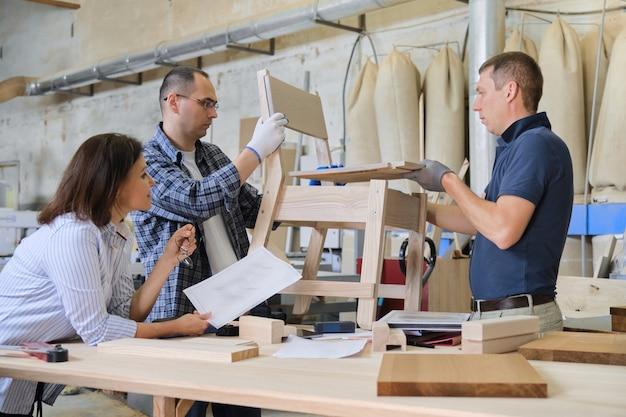 Groep van werkende ontwerpers in timmerwerkplaats
