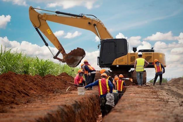 Groep van werknemer en bouwingenieur slijtage veiligheid uniforme afwatering van het afgravingswater