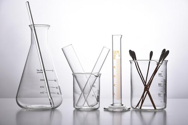 Groep van wetenschappelijk laboratoriumglaswerk met heldere vloeibare oplossing, wetenschappelijk onderzoek en ontwikkelingsconcept. Premium Foto
