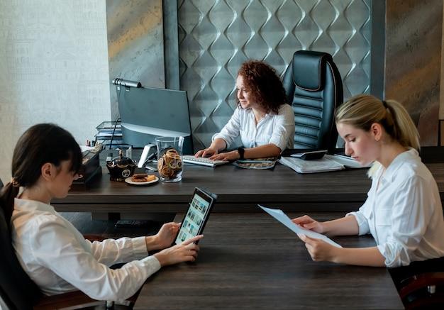 Groep van zakelijke vrouwen zitten aan een bureau met documenten met behulp van laptop en computer met ernstige zelfverzekerde uitdrukking samen te werken in kantoor